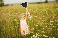 Petite fille avec amour de plat Photos stock