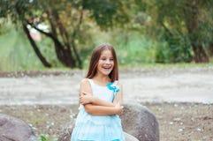 Petite fille avec de longs cheveux dans un portrait de robe, avec émotion souriant et riant, allumage naturel dehors images libres de droits