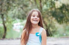 Petite fille avec de longs cheveux dans un portrait de robe, avec émotion souriant et riant, allumage naturel dehors images stock