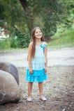 Petite fille avec de longs cheveux dans un portrait de robe, avec émotion souriant et riant, allumage naturel dehors photographie stock libre de droits