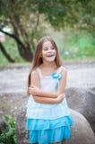 Petite fille avec de longs cheveux dans un portrait de robe, avec émotion souriant et riant, allumage naturel dehors image stock