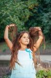 Petite fille avec de longs cheveux en portrait de robe, cheveux d'ascenseurs, allumage naturel dehors photos libres de droits