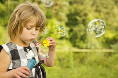 Petite fille avec des bulles de savon Photos stock