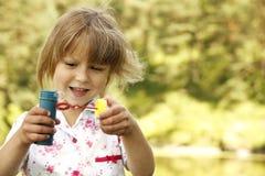 Petite fille avec des bulles de savon Image stock