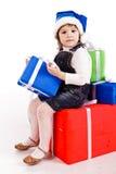Petite fille avec des cadres de cadeau dans le chapeau de Santa Photos libres de droits