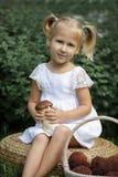 Petite fille avec des champignons à disposition sur la pelouse verte Photos stock