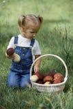 Petite fille avec des champignons à disposition sur la pelouse verte Photographie stock
