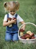 Petite fille avec des champignons à disposition sur la pelouse verte Image libre de droits