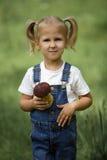 Petite fille avec des champignons à disposition sur la pelouse verte Images libres de droits