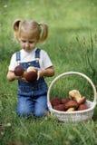 Petite fille avec des champignons à disposition sur la pelouse verte Photos libres de droits
