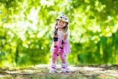 Petite fille avec des chaussures de patin de rouleau en parc Image libre de droits