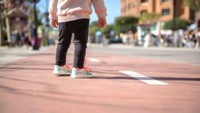 Petite fille avec des espadrilles et des leggins se tenant au-dessus d'une piste de ville Photographie stock