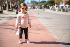 Petite fille avec des espadrilles se tenant au-dessus d'une piste de ville Images libres de droits