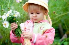 Petite fille avec des fleurs, 2.5 ans Photographie stock libre de droits