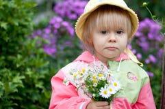 Petite fille avec des fleurs, 2.5 ans Photo libre de droits