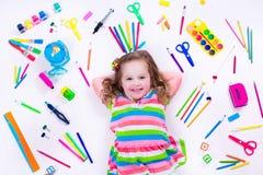 Petite fille avec des fournitures scolaires Photo stock