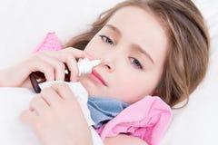Petite fille avec des gouttes pour le nez de mauvaise utilisation à froid. Image libre de droits