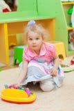 Petite fille avec des jouets dans la salle de jeux Photos libres de droits