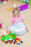 Petite fille avec des jouets dans la salle de jeux Images libres de droits