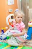 Petite fille avec des jouets dans la salle de jeux Image stock