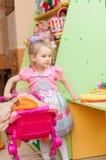 Petite fille avec des jouets dans la salle de jeux Images stock