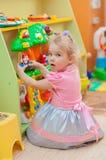 Petite fille avec des jouets dans la salle de jeux Photo stock