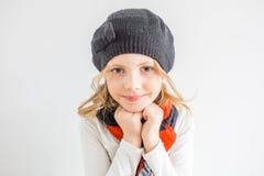 Petite fille avec des mains dans le chapeau noir et le ckarf Photos libres de droits