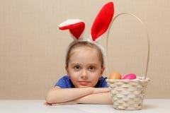 Petite fille avec des oeufs de pâques de panier photo stock