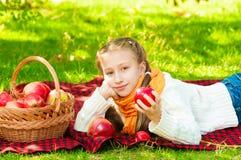 Petite fille avec des pommes en parc Images stock