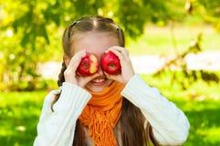 Petite fille avec des pommes en parc Photographie stock libre de droits