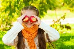 Petite fille avec des pommes en parc Photos libres de droits