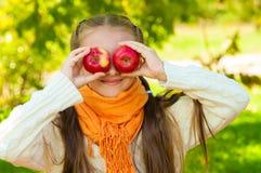 Petite fille avec des pommes en parc Image stock