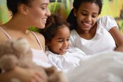 Petite fille avec des soeurs dans le lit Photographie stock