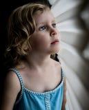 Petite fille avec des yeux bleus regardant la fenêtre fixement Photos libres de droits