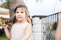 Petite fille avec des yeux bleus touchant ses cheveux Image stock