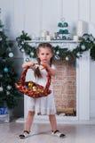 Petite fille avec deux tresses se tenant près d'un arbre de Noël Elle tient un panier avec des jouets Photographie stock