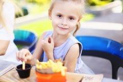 Petite fille avec du charme mangeant des fritures de rench avec de la sauce au café de rue dehors photos stock