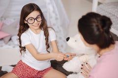 Petite fille avec du charme prenant soin de jouet préféré à la maison Image stock