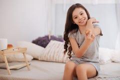Petite fille avec du charme prenant soin de sa blessure à la maison Images stock