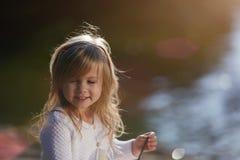 Petite fille avec du charme s'asseyant sur le beau parc Photographie stock libre de droits