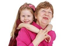 Petite-fille avec du charme étreignant la grand-mère aimée Photographie stock