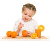 Petite fille avec du jus d'orangeade avec une paille photographie stock