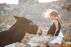 Petite fille avec l'âne sur l'île de Mykonos Photos stock