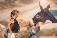 Petite fille avec l'âne sur l'île de Mykonos Photographie stock libre de droits