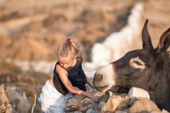 Petite fille avec l'âne sur l'île de Mykonos Image libre de droits