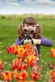Petite fille avec l'animal familier de chiot dans le jardin de tulipe Photos libres de droits