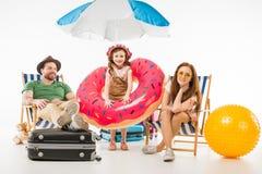 Petite fille avec l'anneau de flottaison se tenant entre les parents s'asseyant sur des canapés du soleil photo libre de droits