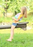 Petite fille avec l'exercice sur une oscillation Photo stock