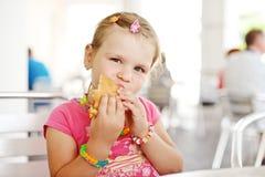 Petite fille avec l'hamburger Photographie stock libre de droits