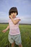 Petite fille avec l'herbe restant sur le pré Images stock